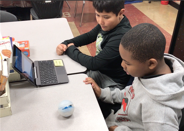 Two students programming a robotic ball